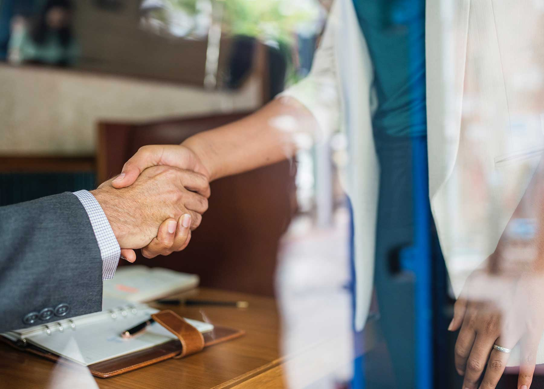 Woman wearing white blazer shakes the hand of a man wearing a blazer